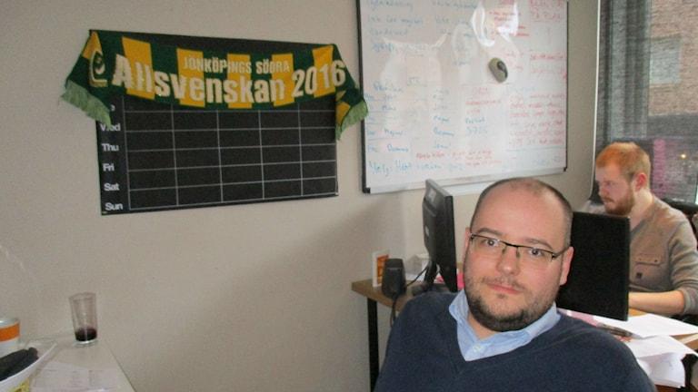 Andreas Söderlund verkkotoimisto JKPG Liven toimituksessa. Hänellä on sininen paita ja harmaa pusero sekä silmälasit.