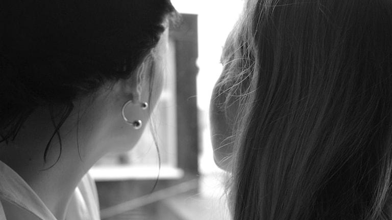 Kaksi tyttöä katsoo ulos ikkunasta.