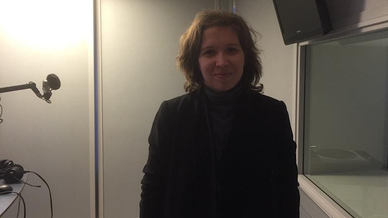 Katja Seitajoki seisoo hämärässä radiostudiossa, tummat vaatteet päällä, katsoen hymyillen kameraan. Kuva: Timo Laine/Sveriges Radio Sisuradio