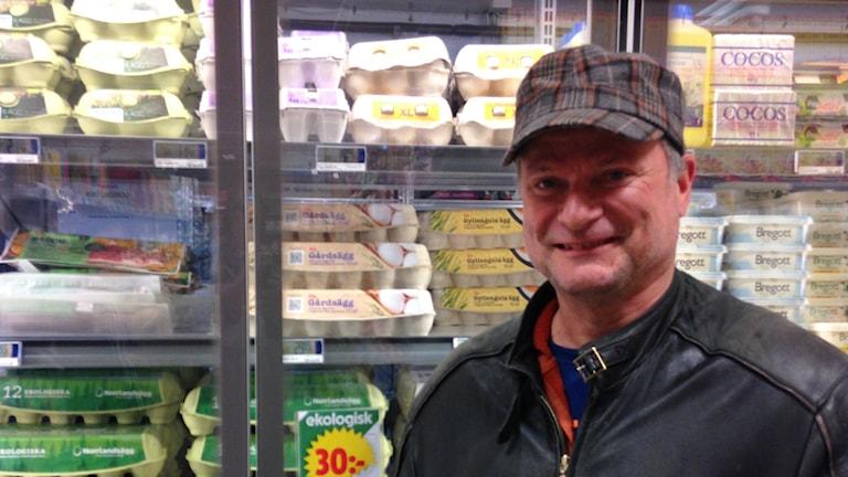 Lucas Lund seisoo nahkatakki päällä ja lippalakki päässä kaupan kananmunakaapin edessä.