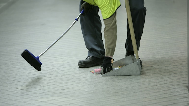 Siivoja, josta nlyy vain kädt ja jalat, on kumartunut noukkimaan roskaa tunnelbanan laiturilta.