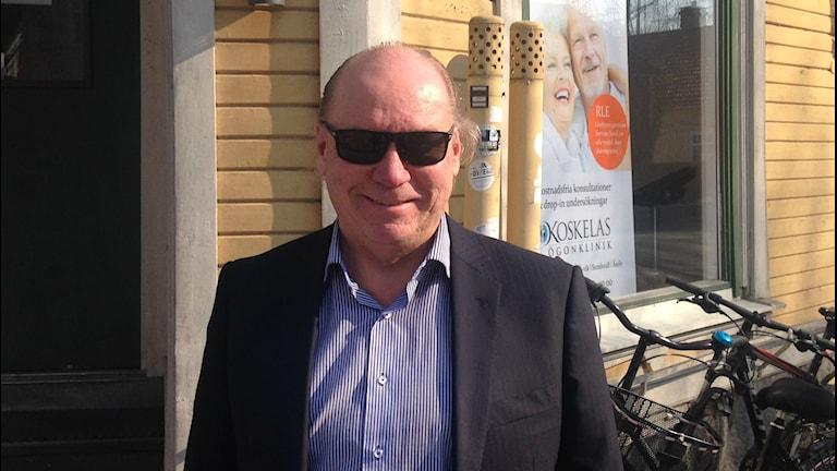 Timo Koskela hymyilee päässään aurinkolasit keltaisen talon edessä.