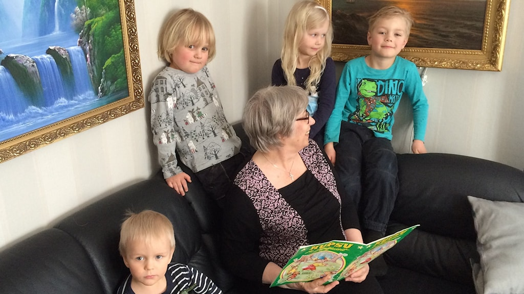 Anneli Heikka ja neljä lastenlasta sohvanurkkauksessa satua lukemassa