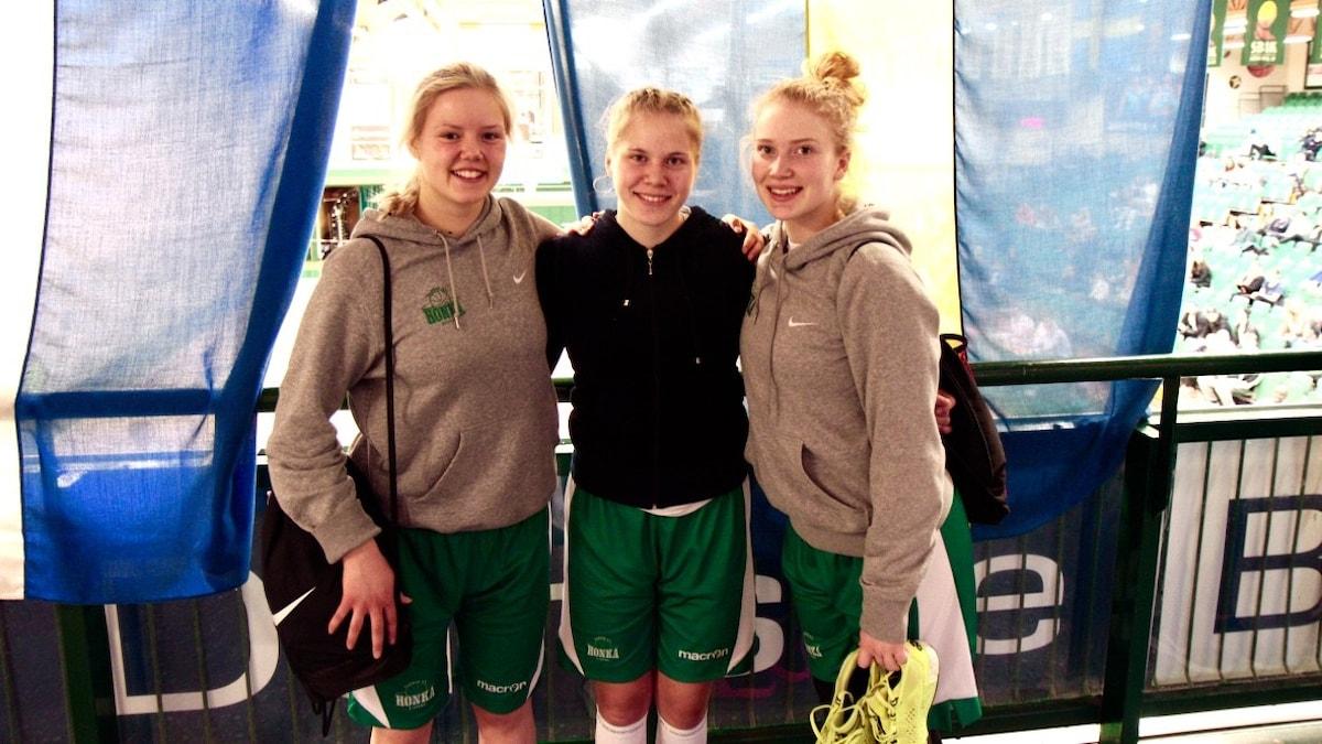 Ronja Orpo, Reetta Sääski och Aino Rauhansalo seisovat lippujen edessä Södertäljen Scania cupissa.