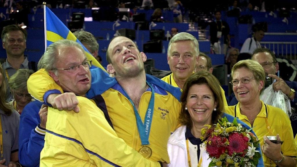 Kuningas Kaarle Kustaa ja Silviä juhlistavat Ruotsin joukkueen kultamitalia.