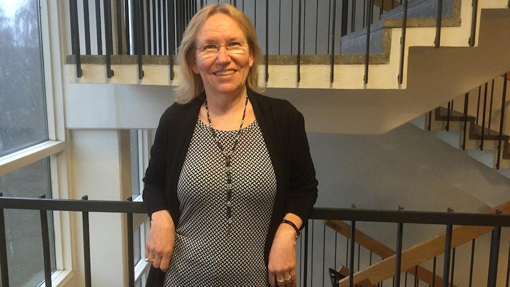 Vaaleatukkainen Pirjo Bakcman Piroth nojailee hymyillen kaiteeseen. Kuva: Timo Laine/Sveriges Radio Sisuradio
