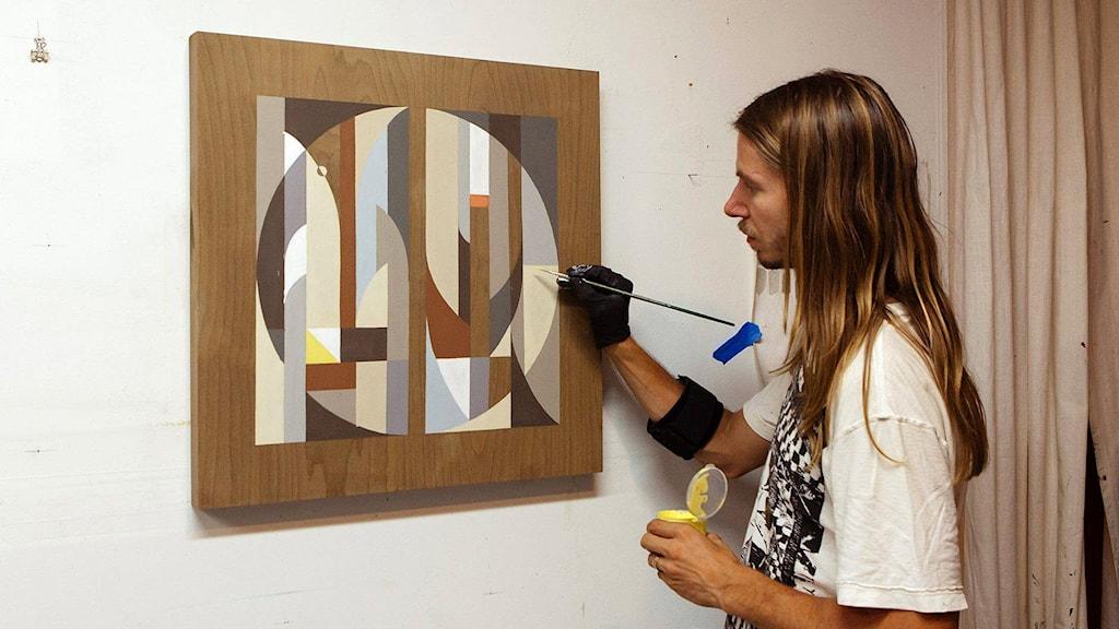 Taiteilija Tony 'Rubin' Sjöman maalaa tauluun graafisia kuvioita.