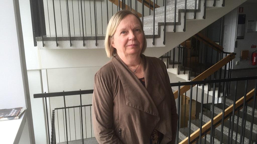 Vaaleahiuksinen Tuula Kuosmanen seisoo ruskeahkossa takissa, portaikko näkyy taustalla. Kuva: Timo Laine/Sveriges Radio Sisuradio