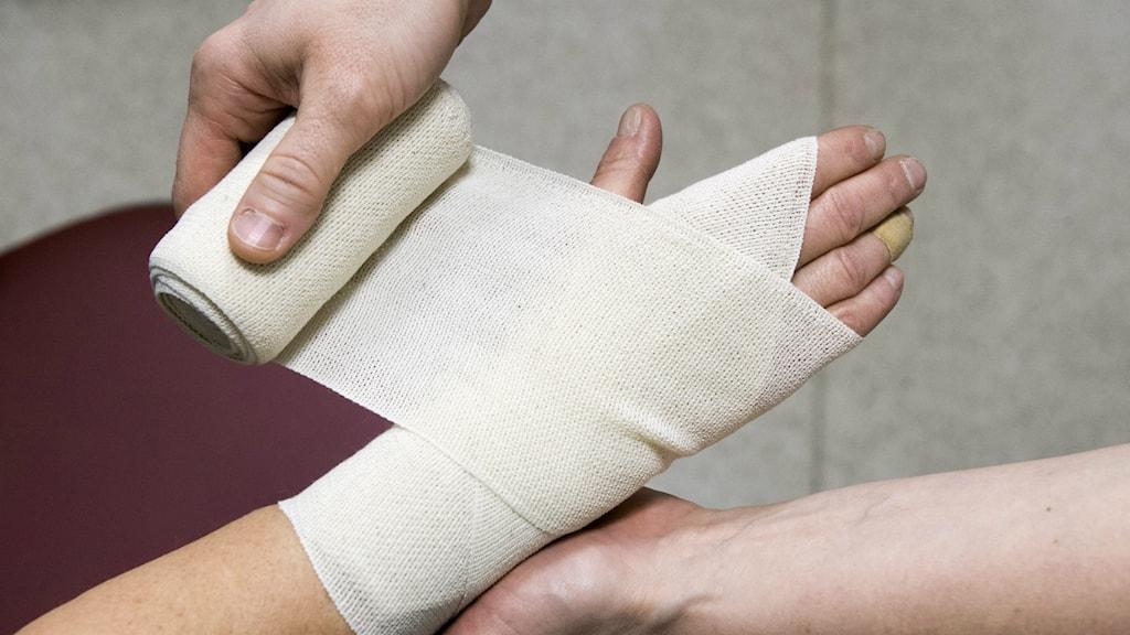 Kuvassa näkyy käsi jonka ympärille kiedotaan sideharsoa.
