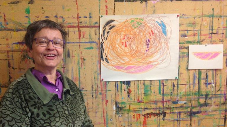 Ulla Kiivuori seisoo värikkään seinän edessä, johon on ripustettu kaksi piirrustusta.