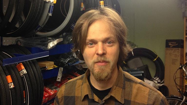 Ruskeapaitainen, parrakas Antti Säisä on polkupyöräkorjaamossaan takanaan pyörän renkaita.