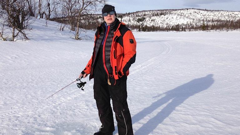 Anne-Riitta Saukkoriipi seisoo jäällä, päällään oranssi takki, mustat housut, kädessään pilkkionki ja taustanaan tunturi jota kohti osoittaa myös hänen varjonsa.