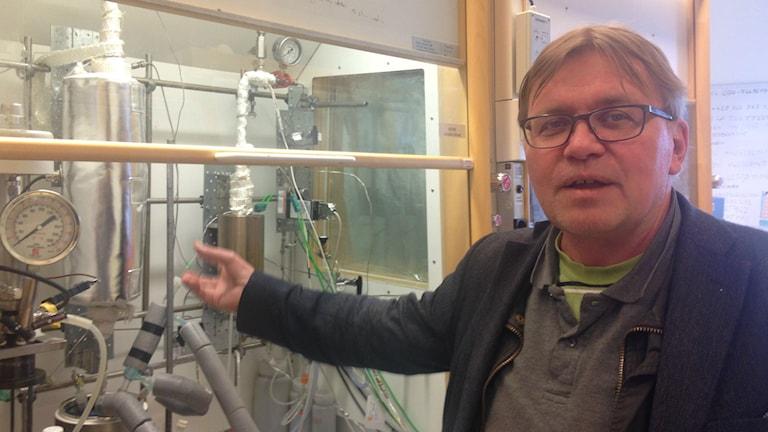 Silmälasipäinen pikkutakki päällä oleva Jyri-Pekka Mikkola osoittaa oikealla kädellään laboratoriokaapin laitteita.