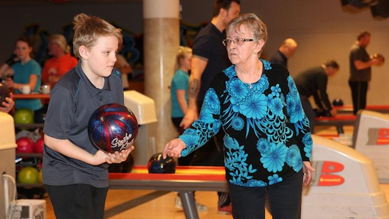 En pojke och en äldre kvinna bowlar tillsammans