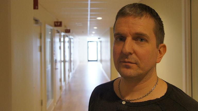 Mikael Koskenniemi seisoo käytävä takanaan.