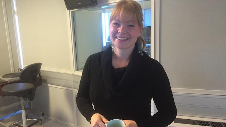 Hymyilevä Saana Tyyskä Preste sininen kahvikuppi kädessää radiostudiossa. Kuva: Timo Laine/Sveriges Radio Sisuradio