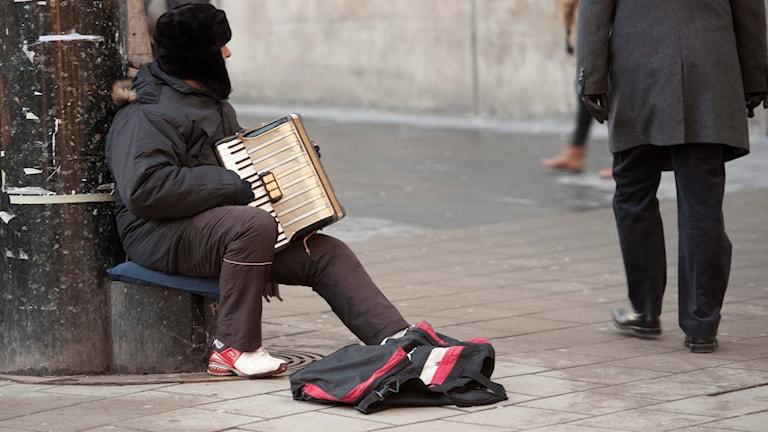 En man spelar dragspel på gatan