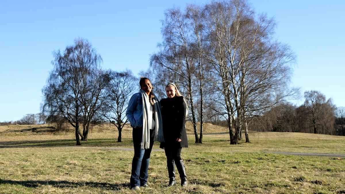 Annabel Aroka ja Anna Viitajylhä seisovat ruohikolla suurien koivujen edessä.