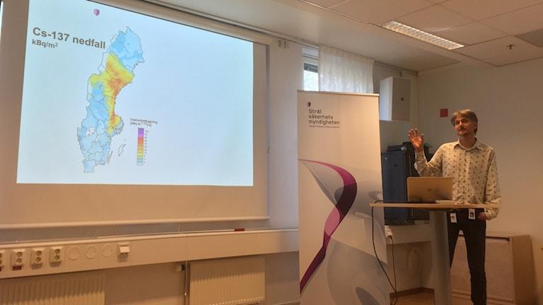 Kuvassa oikealla mies puhuu käsi ylhäällä, keskellä kuvaa on säteilytyrvaviraston banneri ja vasemmassa laidassa valkokankaalle heijastettu kuva Ruotsin kartasta.