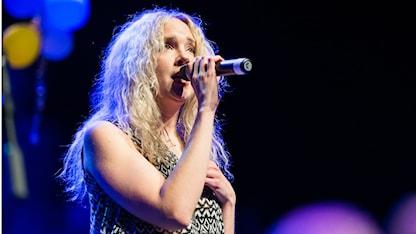 Vaaleatukkainen Sanna Ruohoniemi laulaa mikrofoni kädessäään