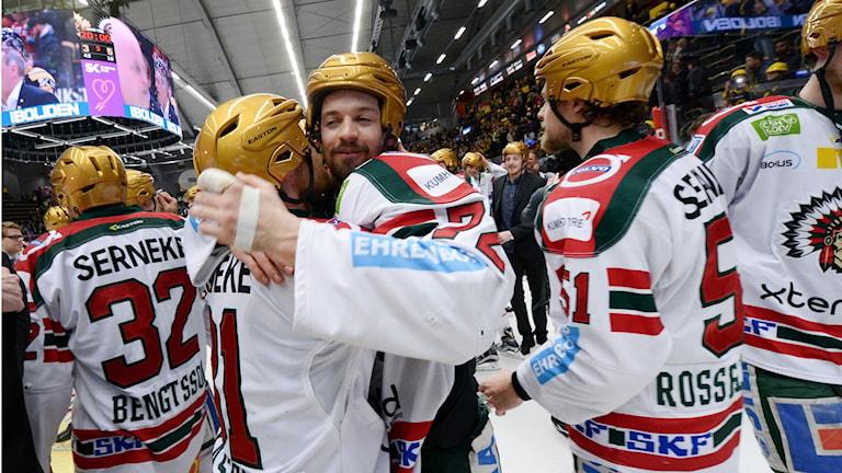 Frölundan jääkiekkojoukkueen jäsenet juhlivat kultaiset kypärät päässä.