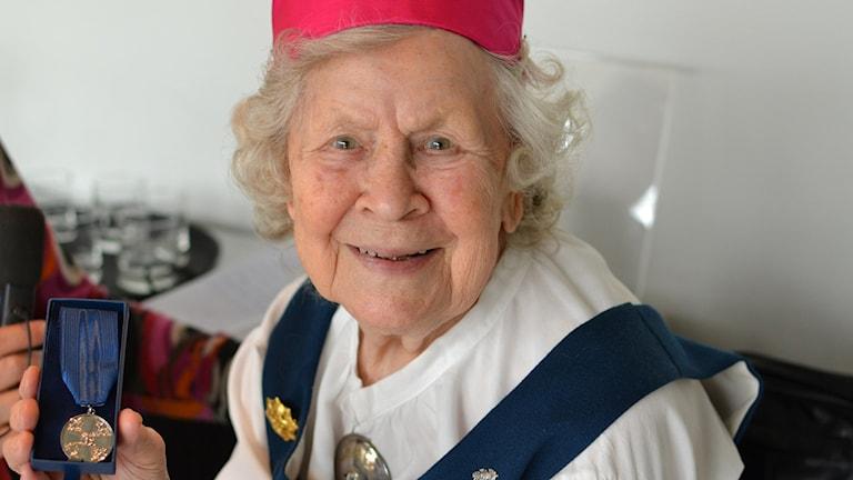 Sotaveteraani Lahja Johansson esittelee veteraanimitaliaan. Hänellä on Laatokan-Karjalan kansallispuku päällään.