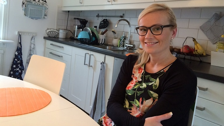 Eija Mustonen Svensson istuu keittiössään kauniisti hymyillen