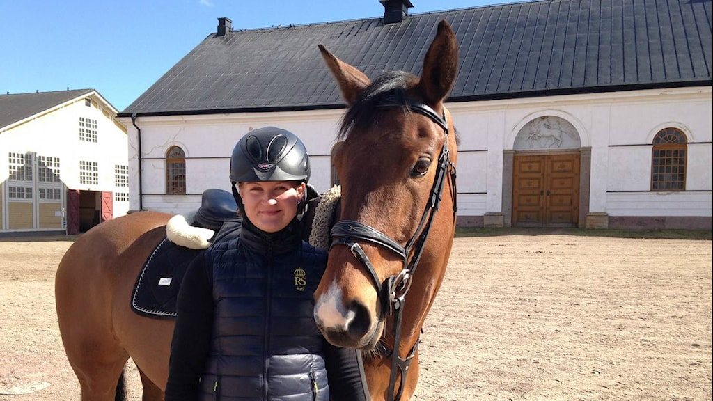 Kati Ojala seisoo ratsastusvarusteissa ja kypärä päässä ruskean hevosen kanssa hiekkakentällä, valkoisen hevotallin edustalla. Foto: Jukka Painilainen SR Sisuradio