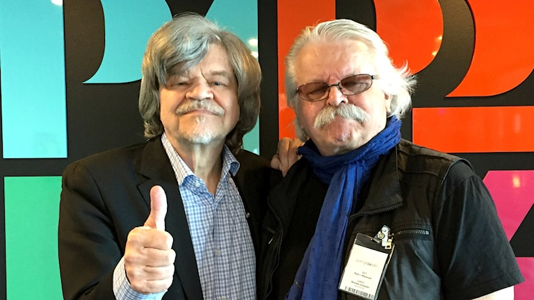 Två män står mot en färgglad bakgrund