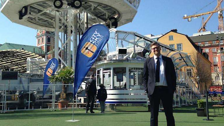 Tukholman kaupungin Euroviisujen projektijohtaja Jesper Ackinger tumma puku päällä aurinkoisessa Kungsträdgårdenissa. Taustalla Euroviisuja varten pystytetty väliaikainen näköalahissi.