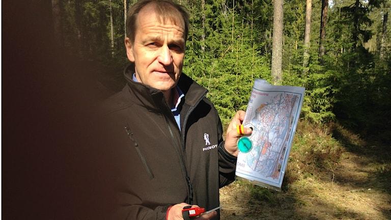 Terho Nevalainen seisoo metsässä valon ja varjon rajalla, vasemmassa kädessään kartta ja peukalokompassi, oikeassa kädessään leimaustikku ja kompassi.
