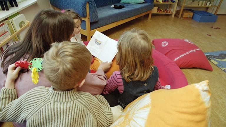 Esikoulunopettaja lukee kirjaa kolmelle lapselle.