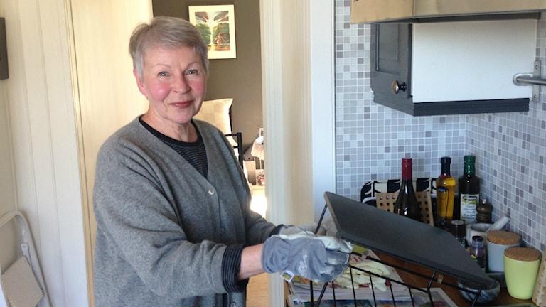 Harmaaseen villatakkiin pukeutuneella Paula Grote Boterilla on käsissään työsormikkaat ja hän esittelee tummanruskeaksi maalaamaansa pikku hyllyä keittiön työpöydällä.