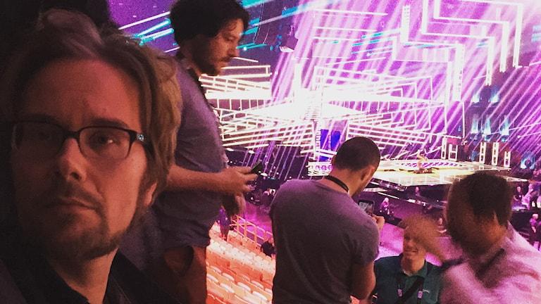 Kuvassa etualalla Erkki Kuronen ja takana ihmisiä, jotka työskentelevät Eurovision laulukilpailujen katsomossa. Taustalla näkyy kilpailun esiintymislava ja siinä erilaisia valoefektejä. Kuva: Erkki Kuronen.