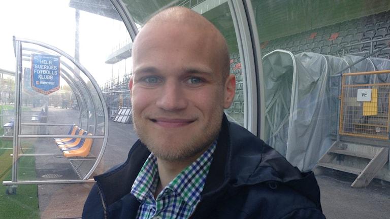 Vili Yrjänä hymyilee jalkapallokentän vaihtoaitiossa taustanaan tyhjä katsomo.