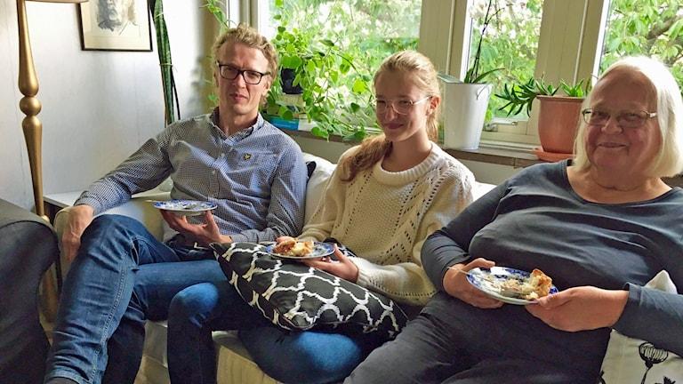 Jukka, Ellen ja Anja Metsola istuvat vierekkäin sohvalla.