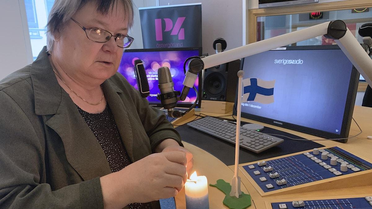 Pirjo Rajalakso radiostudiossa sytyttämässä sinivalkoista kynttilää, pöydällä myös puinen suomen lippu