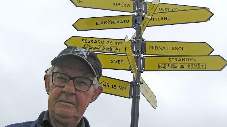 En äldre man vid vägskyltar.