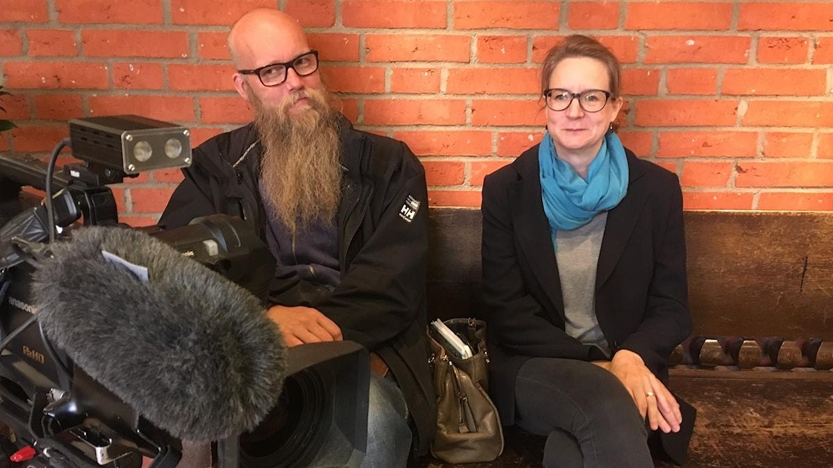 Tuomas Stedt istuu kameransa takana Karita Lehikoinen Stedtin vieressä Trollhättanin Folkets Hus-aulan punatiiliseinustalla