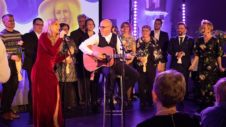 Kaikki ehdokkaat ovat lavalla punamekkoisen lauaja Krista Siegfridsin ja hänen kitaristi Ben Bergmanin takana. Foto: Micke Grönberg.