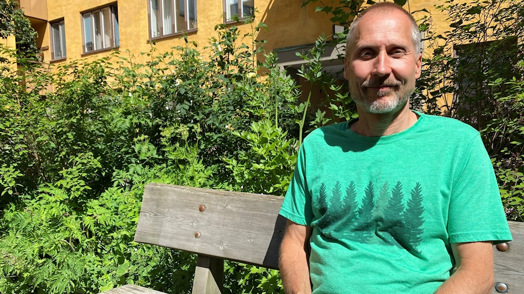 Vihreäpaitainen Jukka Törrönen istuu aurinkoisella penkillä ja katsoo hymyillen kameraan, taustallaan vihreitä pensaita. Kuva: Timo Laine/Sveriges Radio