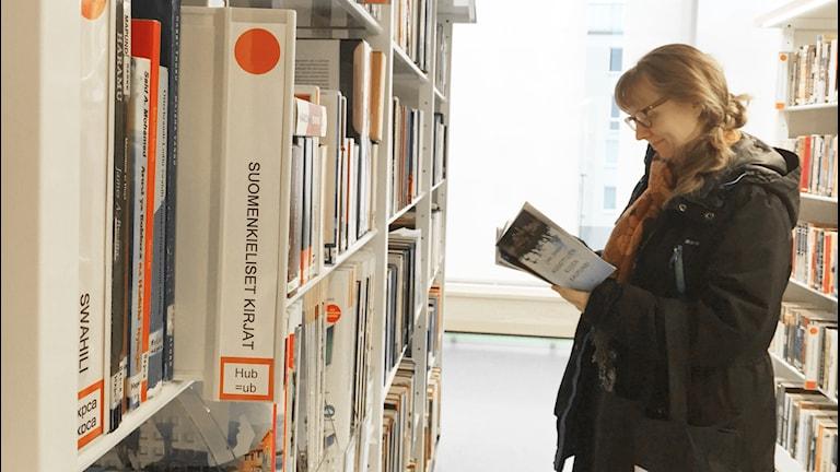 Nainen lukee kirjaa kirjastossa suomenkielisten kirjojen hyllyn vieressä.