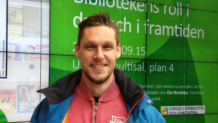 Stefan Öhman seisoo Uumajan kirjaston valotaulun edessä päällään vaalean sininen takki.