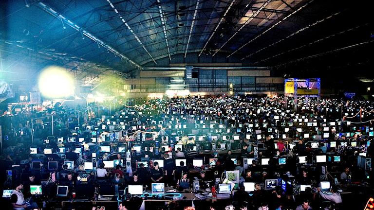 Suuri hämärä halli täynnä kirkkaana loistavia tietokonenäyttöjä