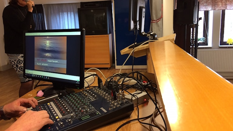 Ett mixerbord och i bakgrunden synd en sångare.