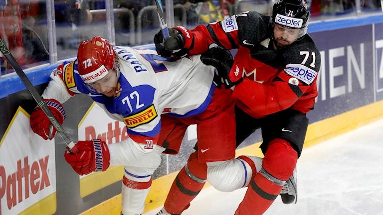 Kuvassa Oikealla oleva Kanadan pelaaja töntää vasemmalla olevaa Venäjän pelajaa kaukalon laittaan. Kuva: Petr David Josek