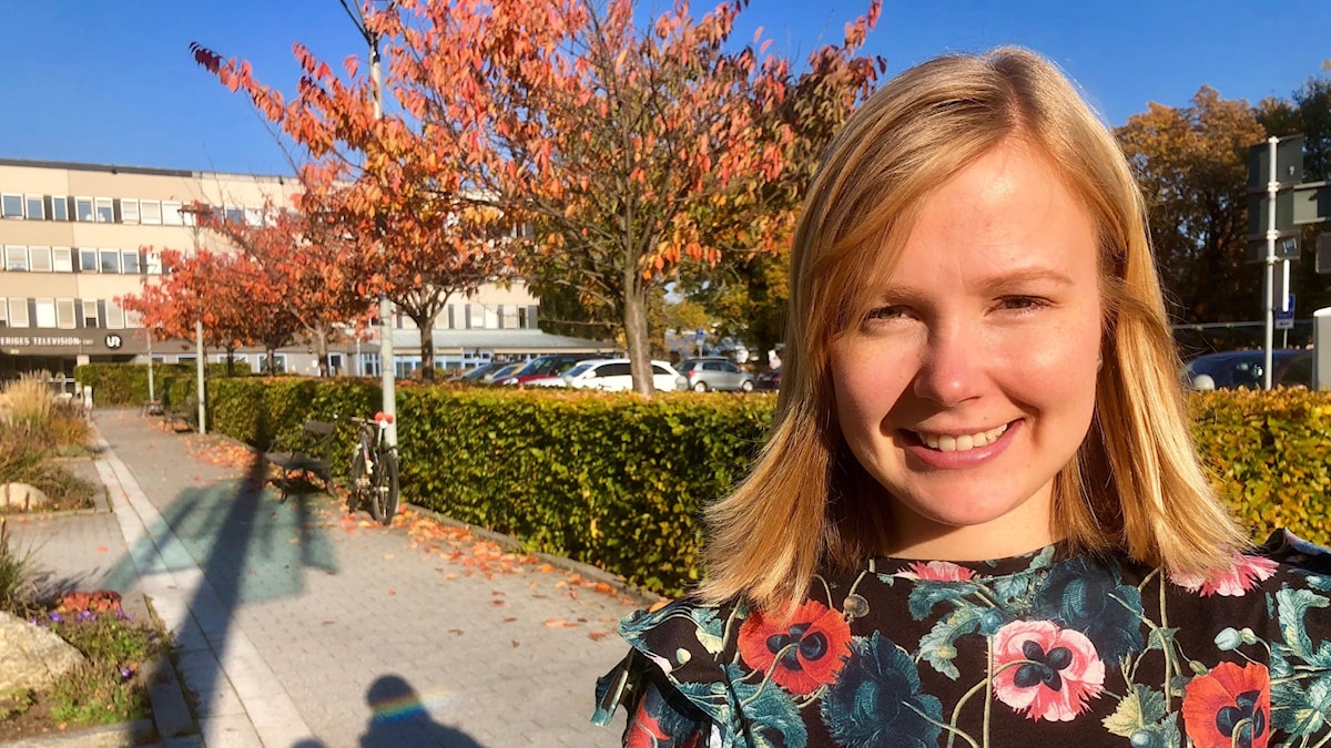Nauravainen, vaaleatukkainen Noora Ottman aurinkoisessa säässä katsoo kameraan takanaan ruskassa olevia puita. Kuva: Timo Laine/SR Sisuradio