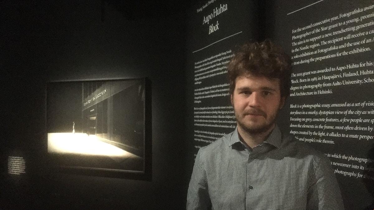 Aapo Huhta seisoo mustassa näyttelytilassa, jossa taustalla hänen esittelytestinsä sekä yksi valokuvistaan. Kuva: Timo Laine/Sveriges Radio Sisuradio