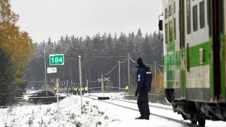 Kuvassa luminen maisema jossa mies seisoo junaraiteen vieressä onnettomuuspaikalla.
