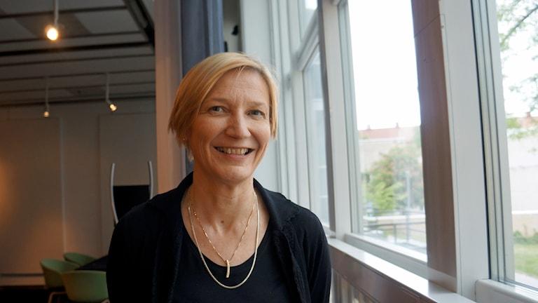 Elina Mäki-Torkko seisoo hymyillen ikkunan ääressä